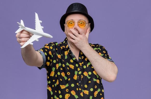 Überraschter erwachsener slawischer mann mit schwarzem hut mit sonnenbrille, der die hand auf den mund legt und das flugzeugmodell hält