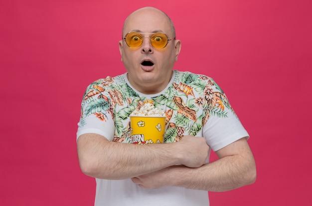 Überraschter erwachsener slawischer mann mit sonnenbrille, der popcorneimer hält
