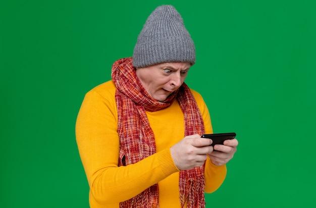 Überraschter erwachsener slawischer mann mit wintermütze und schal um den hals, der das telefon hält und betrachtet