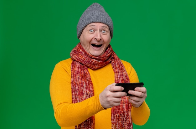 Überraschter erwachsener slawischer mann mit wintermütze und schal um den hals, der telefon hält