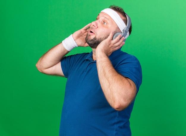 Überraschter erwachsener slawischer sportlicher mann mit kopfhörern, der stirnband und armbänder trägt und seitlich isoliert auf grüner wand mit kopienraum schaut