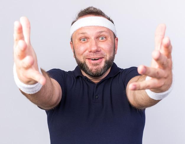 Überraschter erwachsener slawischer sportlicher mann mit stirnband und armbändern, der die hände isoliert auf weißer wand mit kopierraum ausstreckt