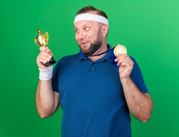 Überraschter erwachsener slawischer sportlicher mann mit stirnband und armbändern, der goldene medaille hält und den siegerpokal einzeln auf grüner wand mit kopienraum betrachtet
