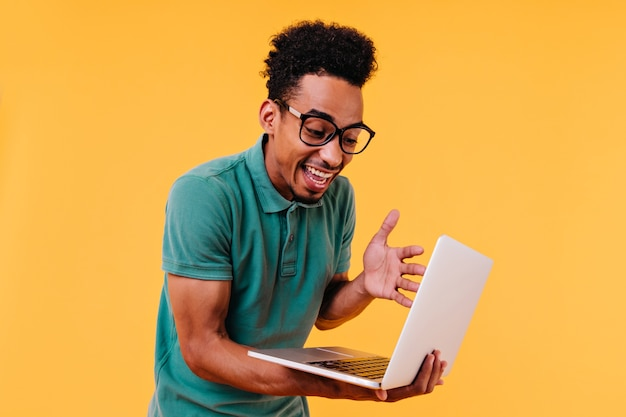 Überraschter gelockter männlicher student, der laptop-bildschirm betrachtet. innenaufnahme des afrikanischen freiberuflers trägt brille.