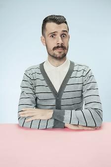 Überraschter geschäftsmann, der am tisch auf blauem studiohintergrund sitzt. das porträt im minimalismusstil