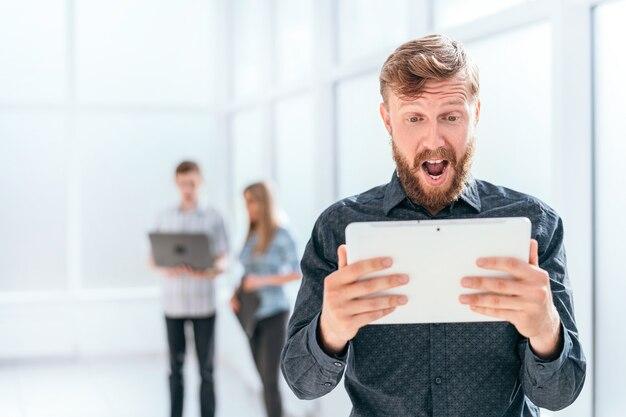 Überraschter geschäftsmann, der den digitalen tablettbildschirm betrachtet
