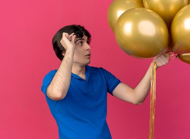 Überraschter, gutaussehender kaukasier hebt eine sonnenbrille und betrachtet heliumballons