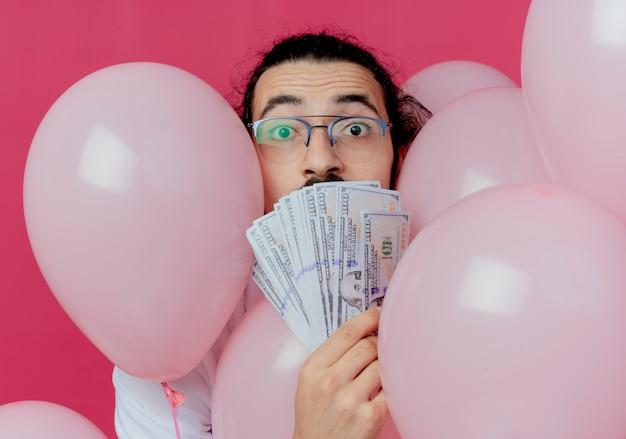 Überraschter gutaussehender mann, der eine brille trägt, die zwischen luftballons steht und mund mit bargeld bedeckt