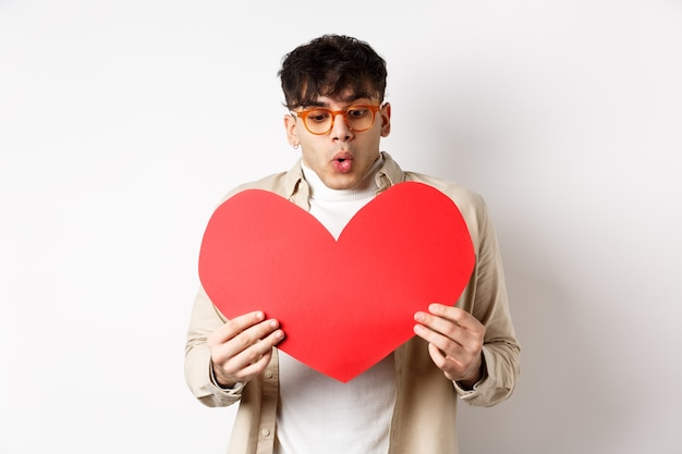 Überraschter gutaussehender mann erhält am valentinstag eine große rote herzpostkarte, betrachtet das geschenk mit erstaunen, genießt den tag der liebenden und steht auf weißem hintergrund.