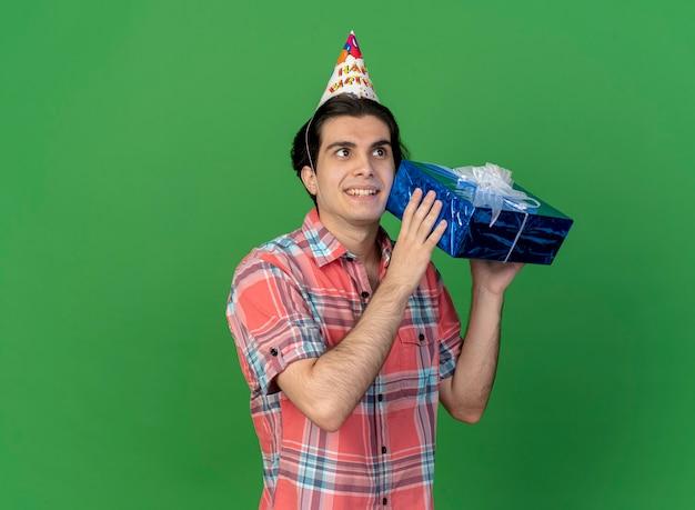 Überraschter hübscher kaukasischer mann mit geburtstagsmütze hält geschenkbox holds