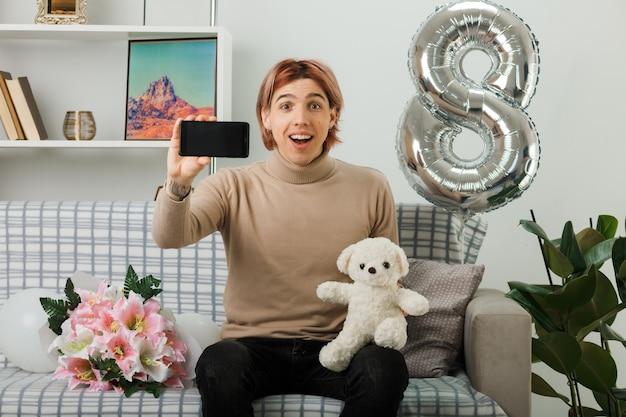 Überraschter hübscher kerl am glücklichen frauentag, der teddybären mit telefon hält, der auf sofa im wohnzimmer sitzt