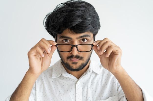 Überraschter intelligenter indischer mann, der die gläser nicht glaubt seine augen justiert.