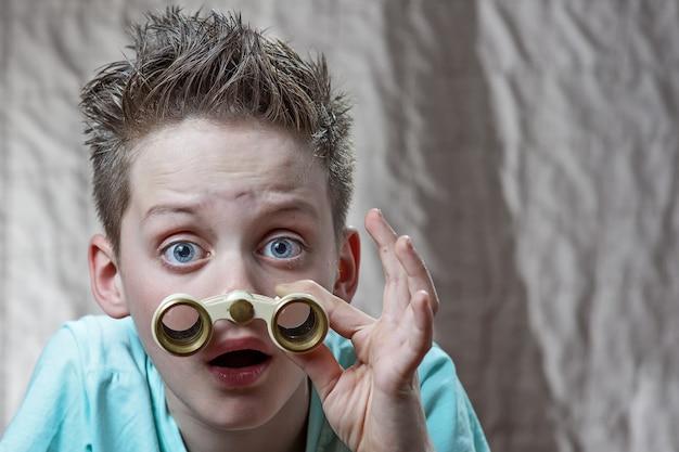 Überraschter jugendlich junge, der emotional durch ferngläser schaut