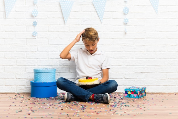 Überraschter junge, der seinen geburtstag mit einem kuchen feiert