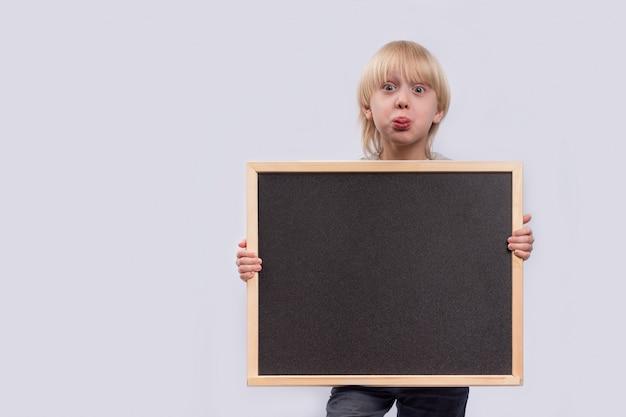 Überraschter junge, der tafel hält. schwarzer kopierraum. vorlage. attrappe, lehrmodell, simulation