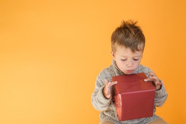 Überraschter junge im pullover, der das geschenk auf orange hintergrund betrachtet.