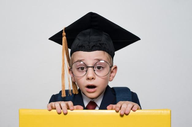 Überraschter junge in der brille, die studentenhut trägt. mittelschule, junior high school.