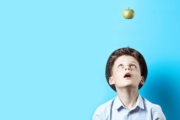 Überraschter junge in einem hellen hemd schaut oben.