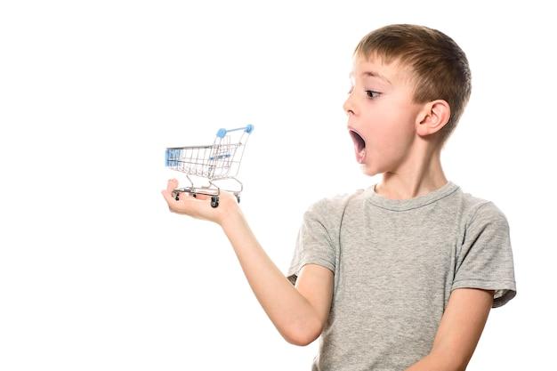 Überraschter junge mit offenem mund, der einen kleinen metalleinkaufswagen auf einer handfläche hält.