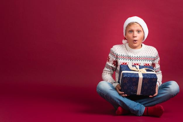 Überraschter junge mit weihnachtsgeschenk