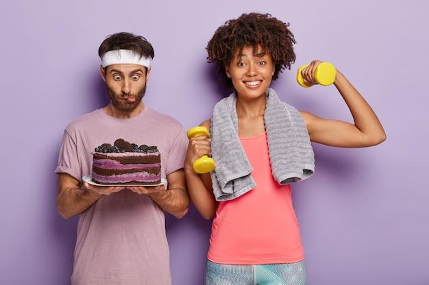 Überraschter junger afro-mann starrt auf köstlichen kuchen, trägt weißes stirnband, fühlt versuchung, glückliche frau arbeitet am bizeps, erhöht gewichte, führt sportlichen lebensstil, steht vor lila hintergrund.