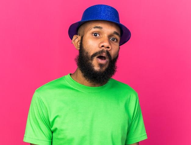 Überraschter junger afroamerikaner mit partyhut isoliert auf rosa wand