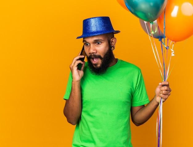 Überraschter junger afroamerikaner mit partyhut und luftballons spricht am telefon