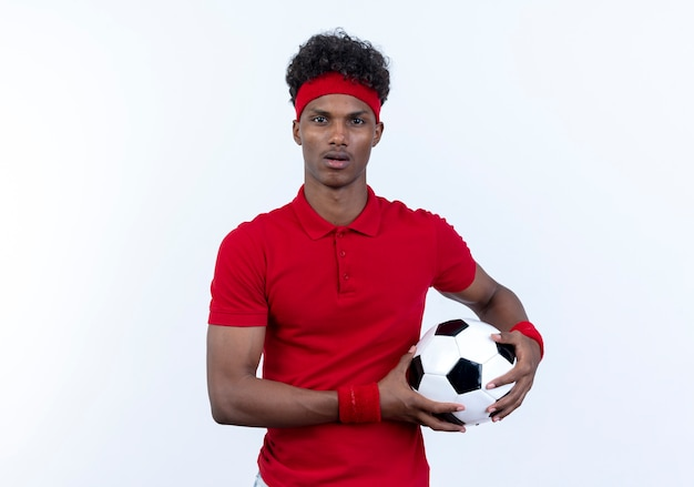 Überraschter junger afroamerikanischer sportlicher mann, der stirnband und armband hält, die kugel lokalisiert auf weiß tragen