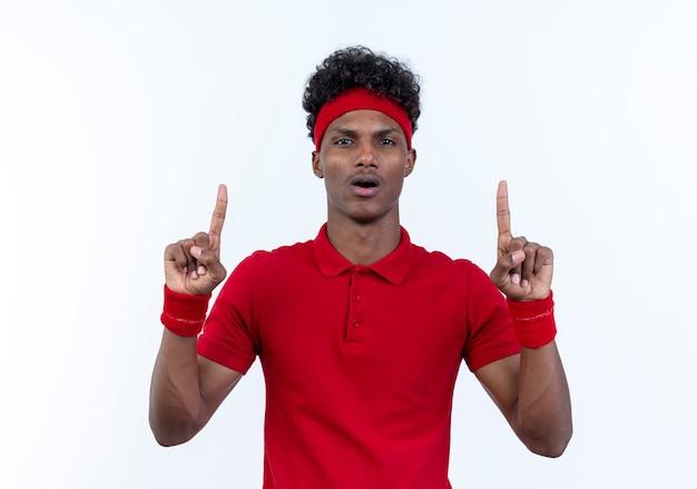 Überraschter junger afroamerikanischer sportlicher mann, der stirnband und armband trägt, zeigt oben auf weiß