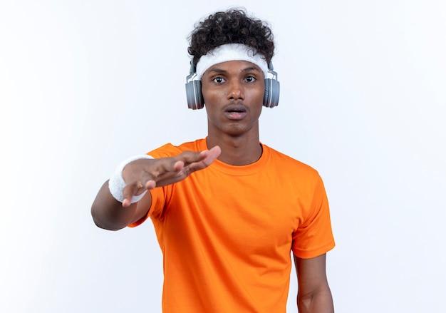 Überraschter junger afroamerikanischer sportlicher mann mit stirnband und armband und kopfhörern, die der kamera die hand reichen