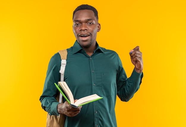 Überraschter junger afroamerikanischer student mit rucksack mit buch und stift