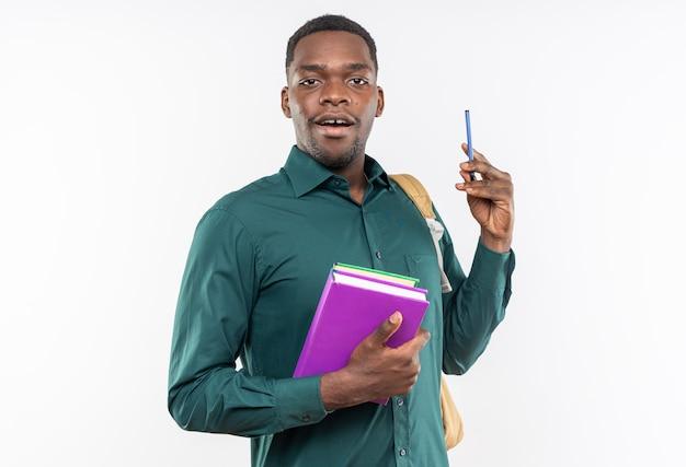 Überraschter junger afroamerikanischer student mit rucksack mit büchern und stift