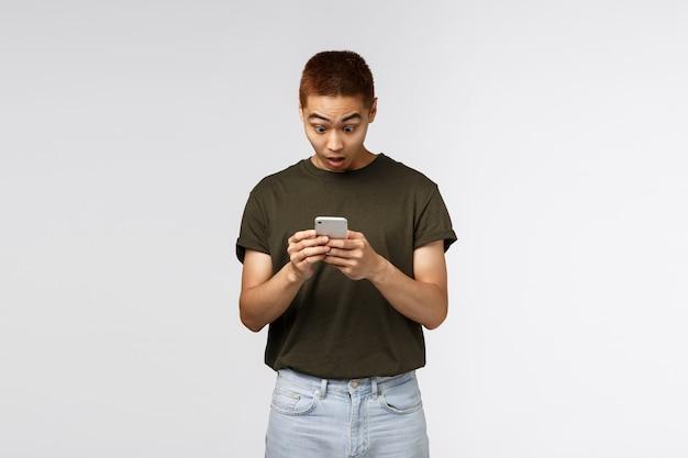 Überraschter junger asiatischer mann, der smartphone betrachtet