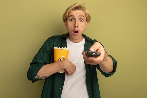 Überraschter junger blonder kerl, der grünes t-shirt hält eimer popcorn mit tv-fernbedienung hält
