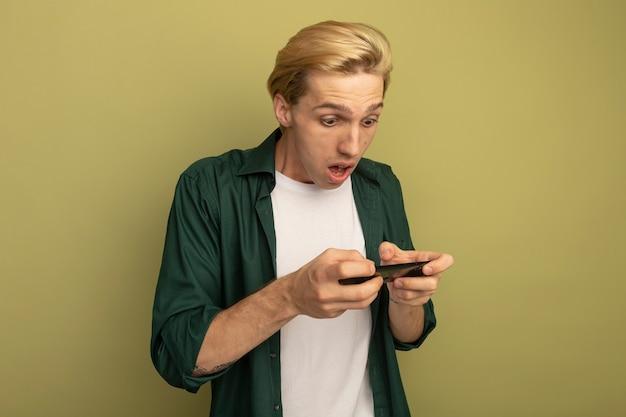Überraschter junger blonder kerl, der grünes t-shirt trägt, das am telefon spielt