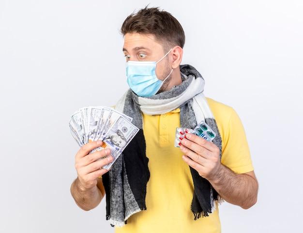 Überraschter junger blonder kranker mann, der medizinische maske und schal trägt, hält geld und packungen von medizinischen pillen, die auf weißer wand lokalisiert werden