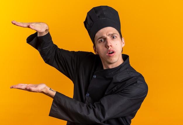 Überraschter junger blonder männlicher koch in kochuniform und mütze, der auf die kamera schaut und die größe geste einzeln auf oranger wand macht