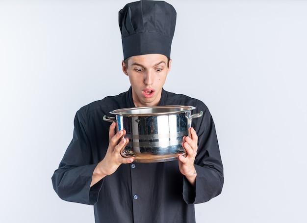 Überraschter junger blonder männlicher koch in kochuniform und mütze, der den topf isoliert auf weißer wand hält und schaut