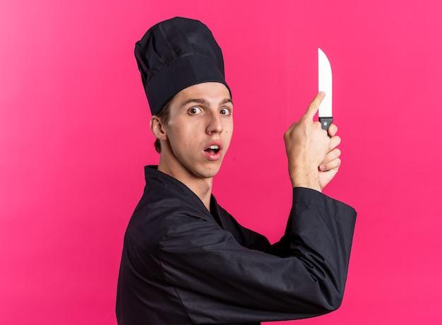 Überraschter junger blonder männlicher koch in kochuniform und mütze, der in der profilansicht steht und das messer mit dem finger hält und berührt, der die kamera isoliert auf rosa wand betrachtet