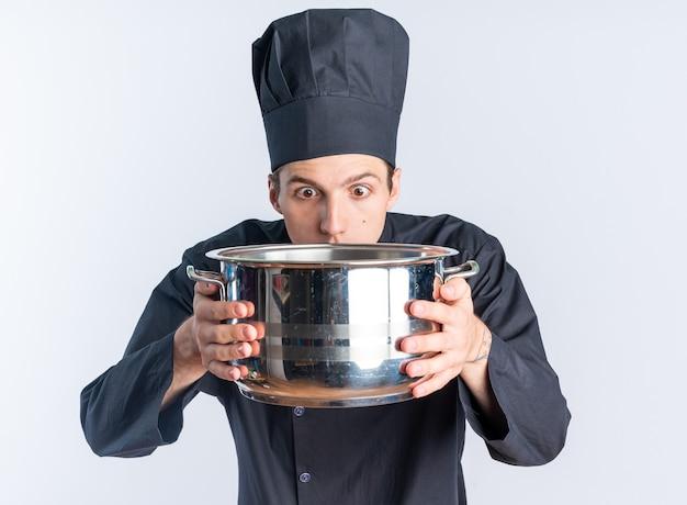 Überraschter junger blonder männlicher koch in kochuniform und mütze, der topf hält und betrachtet