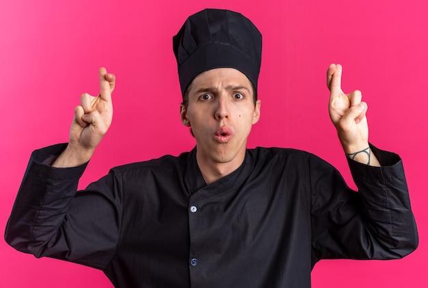 Überraschter junger blonder männlicher koch in kochuniform und mütze mit blick auf die kamera und viel glück geste isoliert auf rosa wand