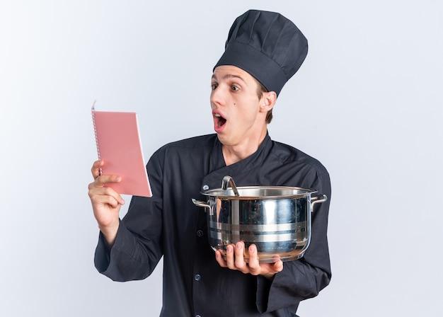 Überraschter junger blonder männlicher koch in kochuniform und mütze mit topflesenotizblock isoliert auf weißer wand