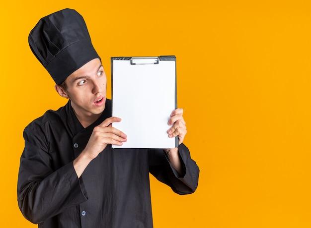Überraschter junger blonder männlicher koch in kochuniform und mütze mit zwischenablage auf der seite isoliert auf oranger wand mit kopierraum