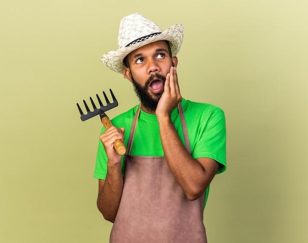 Überraschter junger gärtner afroamerikanischer typ mit gartenhut, der rechen hält und hand auf wange legt
