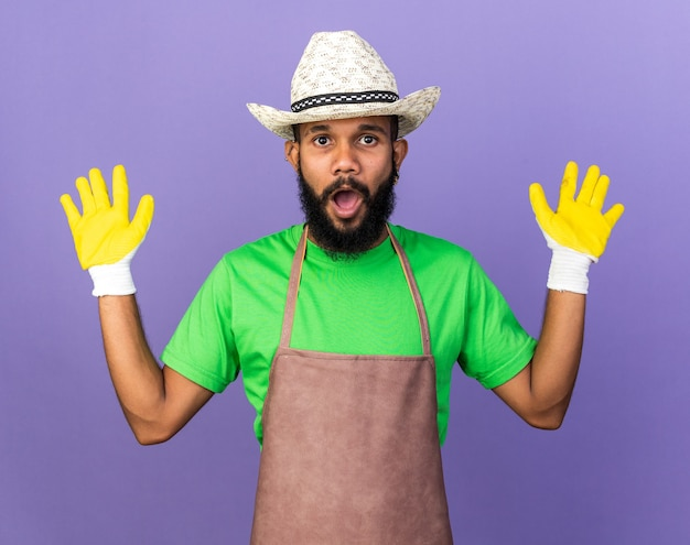 Überraschter junger gärtner, der einen gartenhut mit handschuhen trägt, der die hände isoliert auf blauer wand hebt