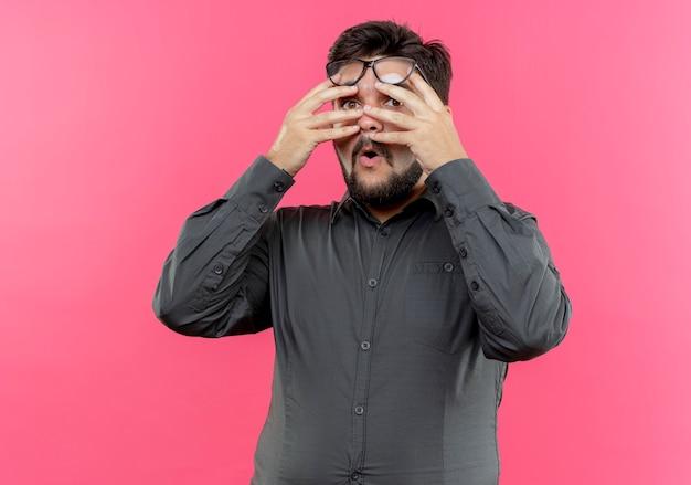 Überraschter junger geschäftsmann, der brille bedecktes gesicht mit den auf rosa lokalisierten händen trägt