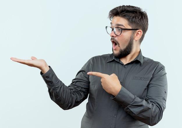 Überraschter junger geschäftsmann, der eine brille trägt, die vorgibt zu halten, und auf etwas zeigt, das auf weiß isoliert ist