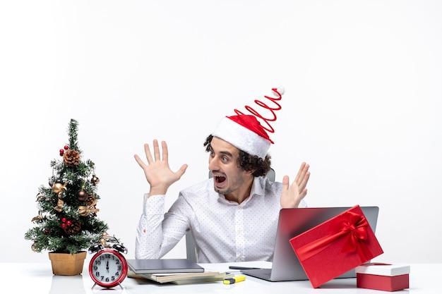 Überraschter junger geschäftsmann mit lustigem weihnachtsmannhut, der weihnachtsbaum verziert und weihnachten im büro auf weißem hintergrund feiert