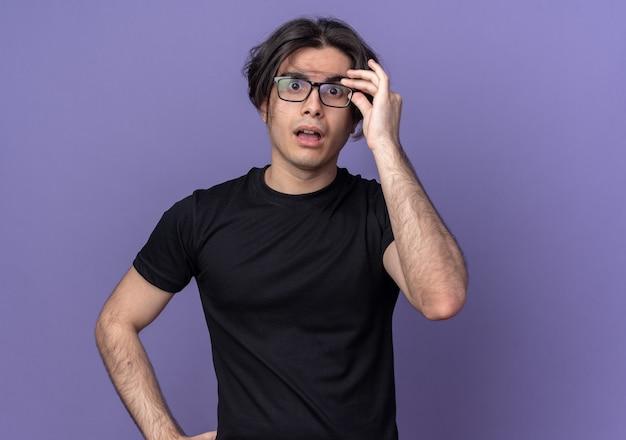 Überraschter junger gutaussehender kerl, der ein schwarzes t-shirt trägt und eine brille trägt und hält, die auf lila wand isoliert ist?