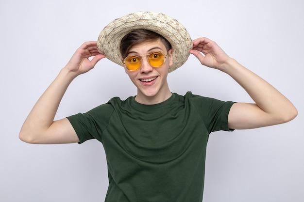 Überraschter junger gutaussehender kerl mit hut mit brille isoliert auf weißer wand